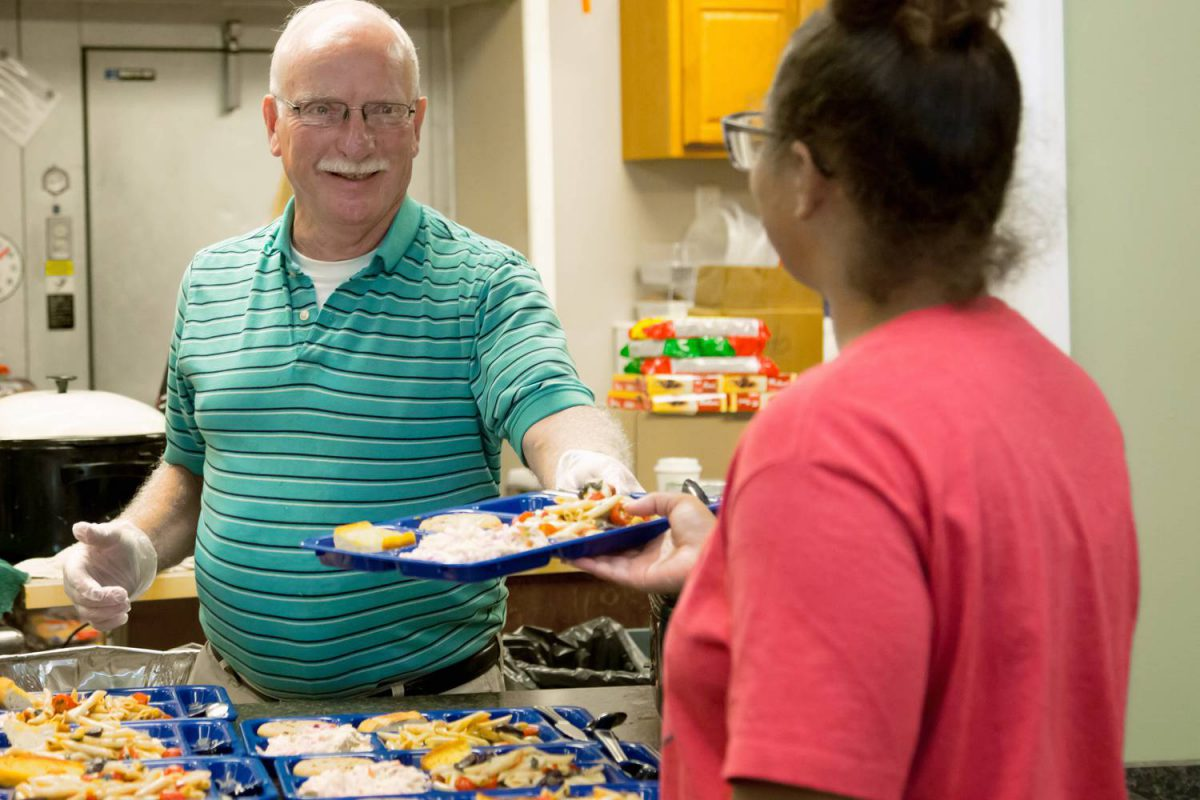 alt=Caucasian man smiling as he serves food to a woman in a pink shirt at the emergency homeless shelter